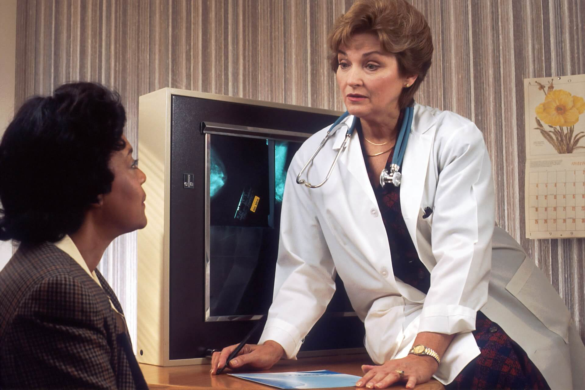 Female doctor sitting on her table talking to a patient