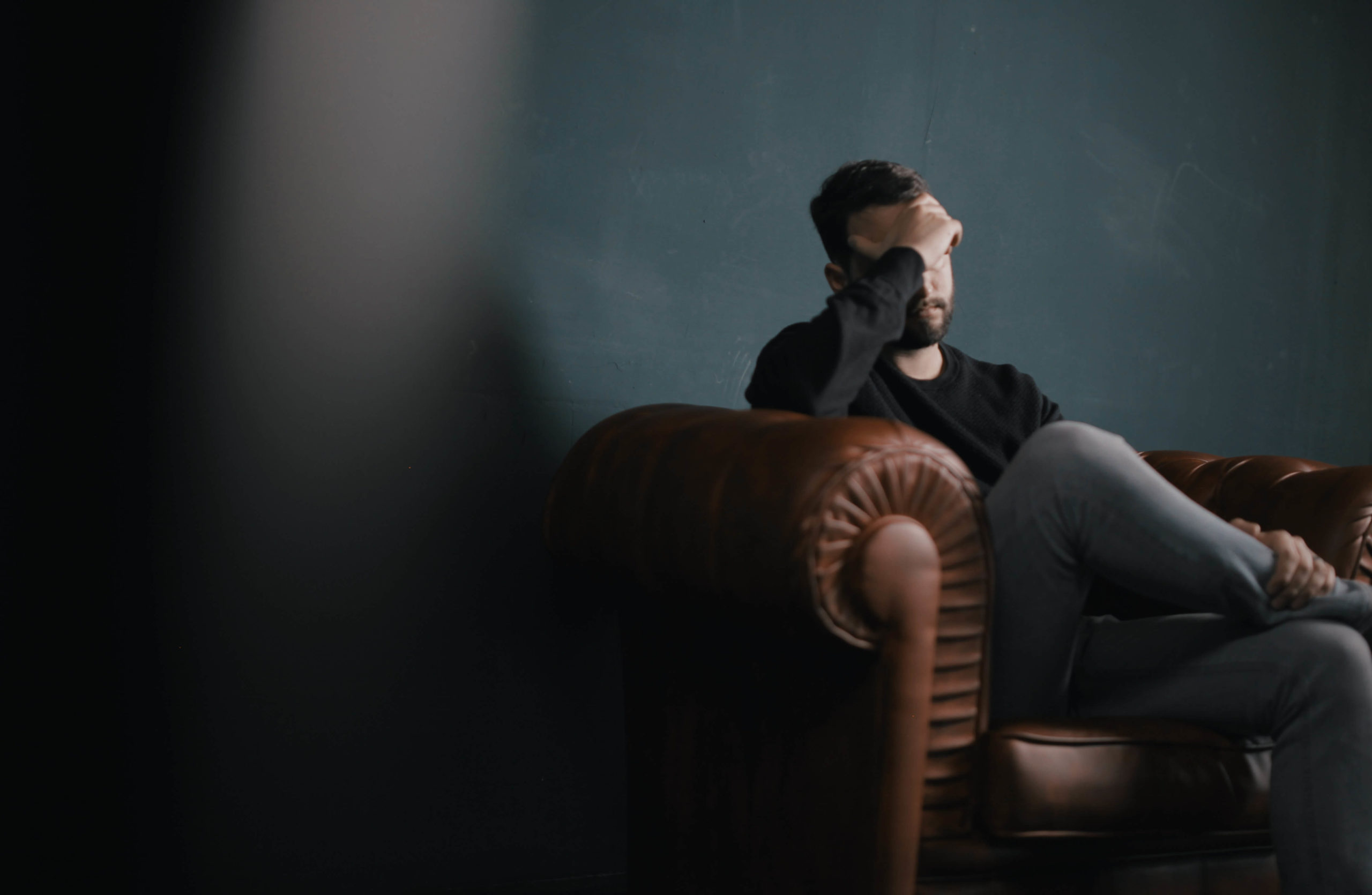 Man sitting on a sofa covering his face