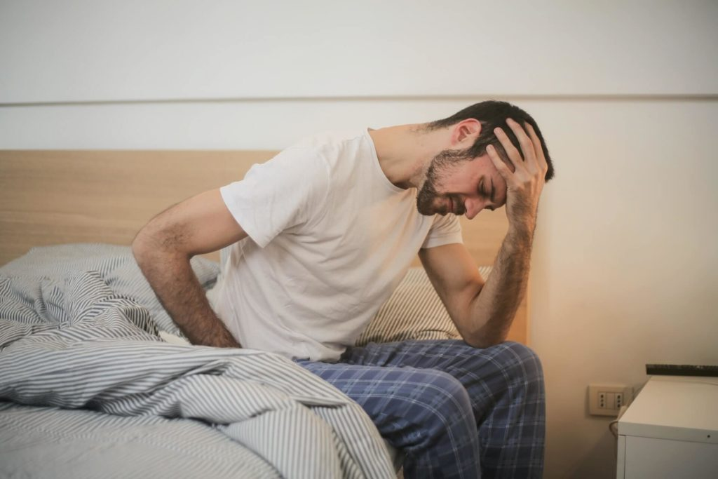 Man holding his head while sitting on bed