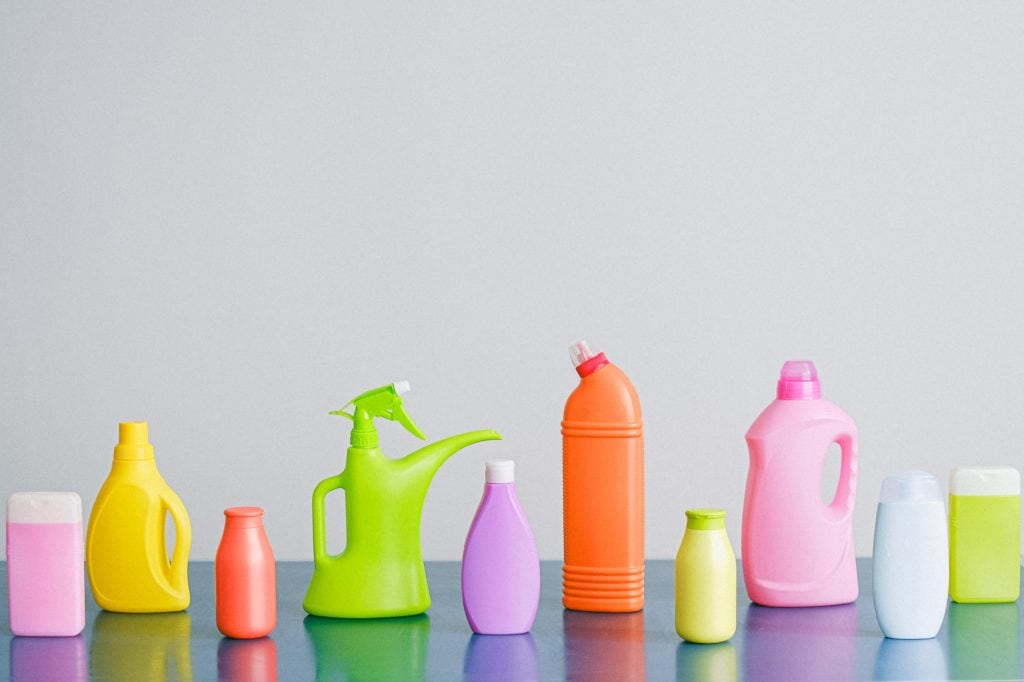 Colorful unlabeled bottles lined up on top of a table