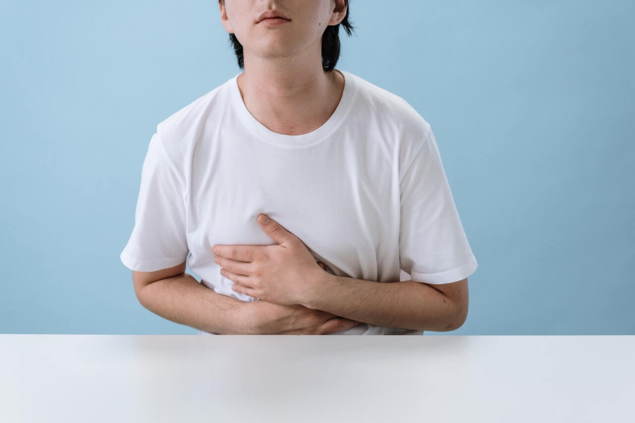 Person in white shirt finding it hard to breathe