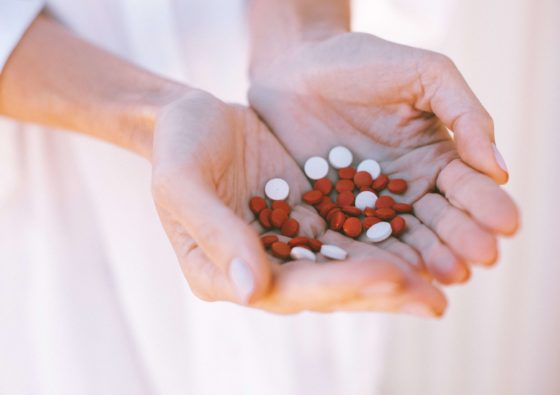 Woman holding red and white pills