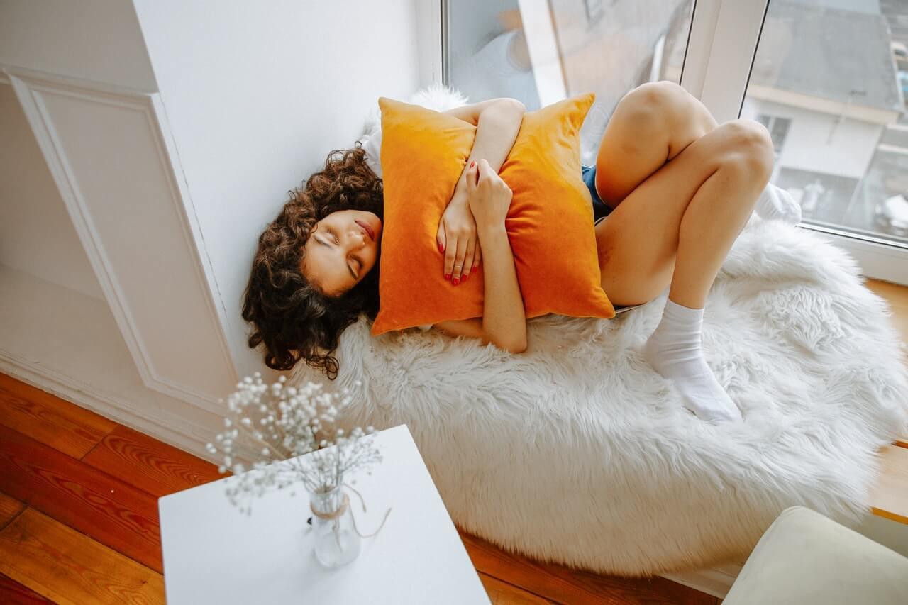 Woman hugging a pillow beside a window