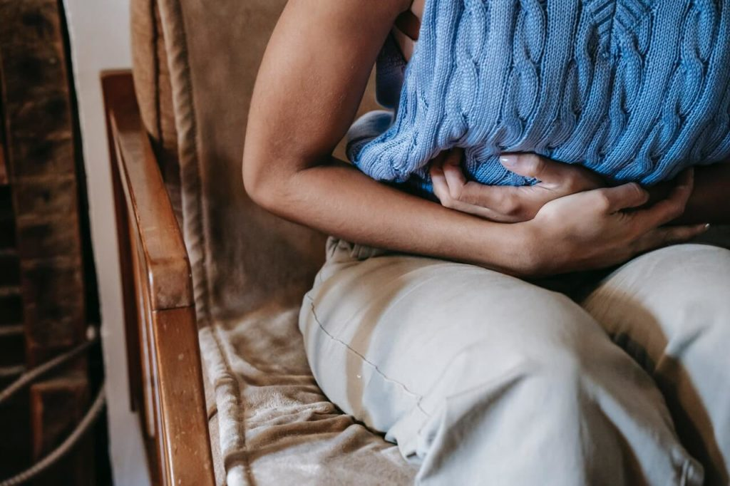 Woman in blue shirt having stomach pain