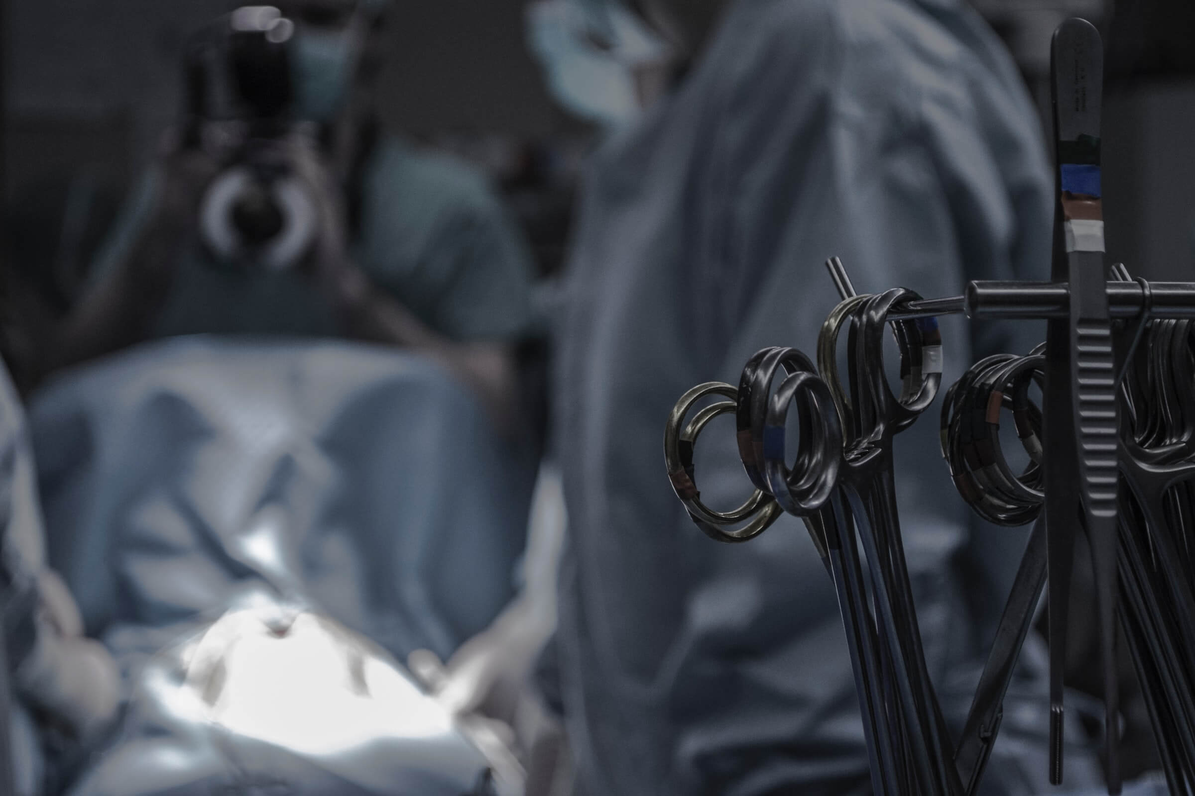 Surgical scissors on close up with doctors in the background