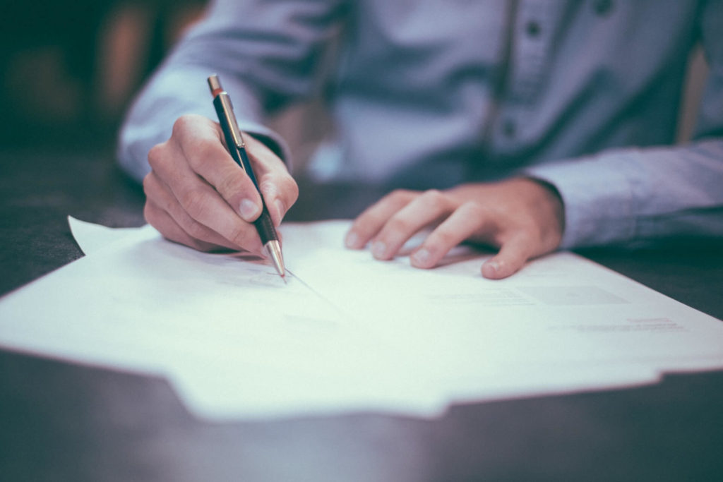 Man writing on paper on top of table