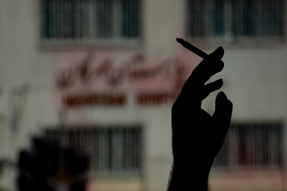 Close up photo of a hand holding cigarette