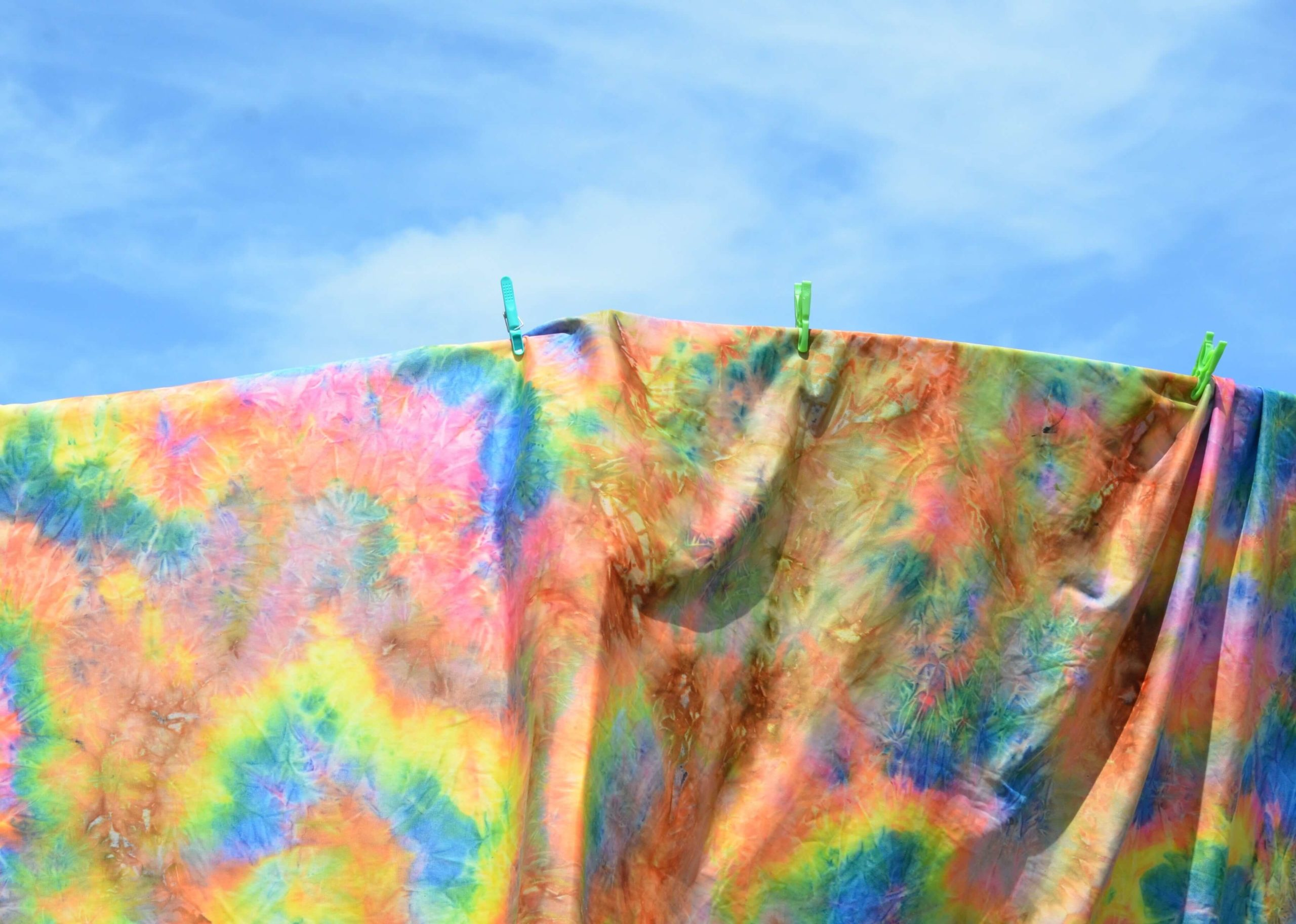 Colorful blanket being dried against a blue background