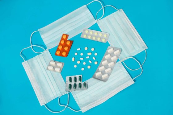 Surgical masks with medications on blue surface