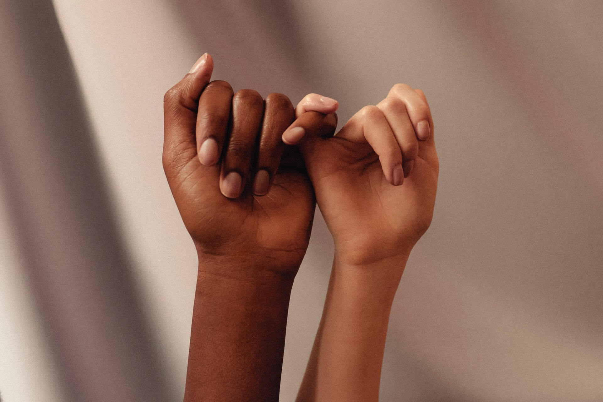 Two women doing pinky promises